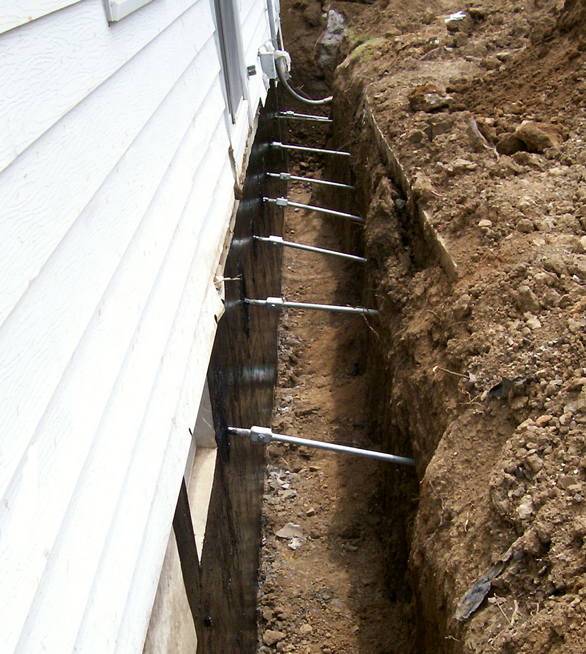 Fixing A Leaning Retaining Wall : Helical piers foundation repair waterproofing and